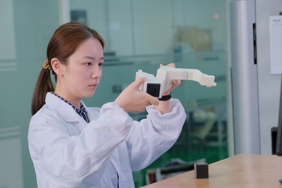 Kohler application engineer Chen Lin examines a 3D printed part.