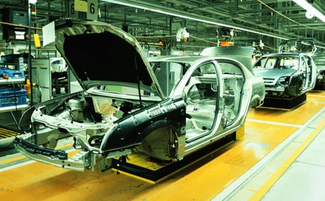 An auto manufacturing assembly line with a car being put together